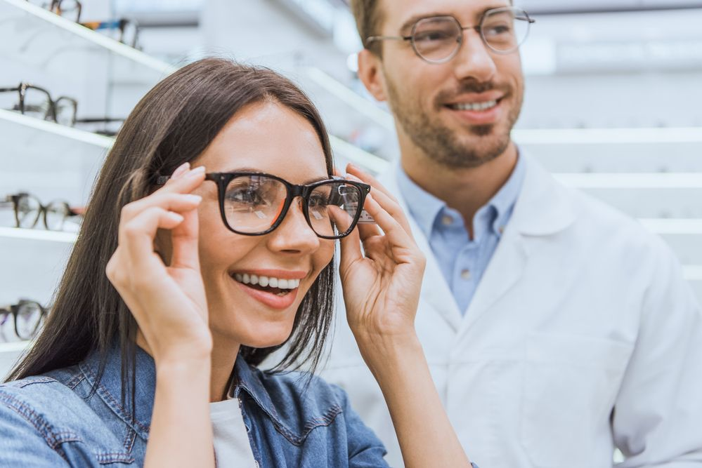 Woman trying on glasses with optometrist